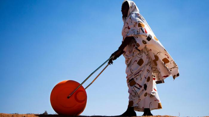 A woman in El Fasher, North Darfur, uses a water roller for easily and efficiently carrying water. With its large drum capacity (usually 75 litres), the device frees women and children from having to spend a large portion of every day dedicated to collecting water for their households. The African Union-United Nations Hybrid Operation in Darfur (UNAMID) has distributed some 3,000 such rollers across Darfur.